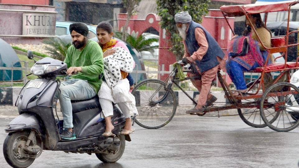 Commuters bear the rain in Amritsar on Saturday. (Sameer Sehgal/ht)