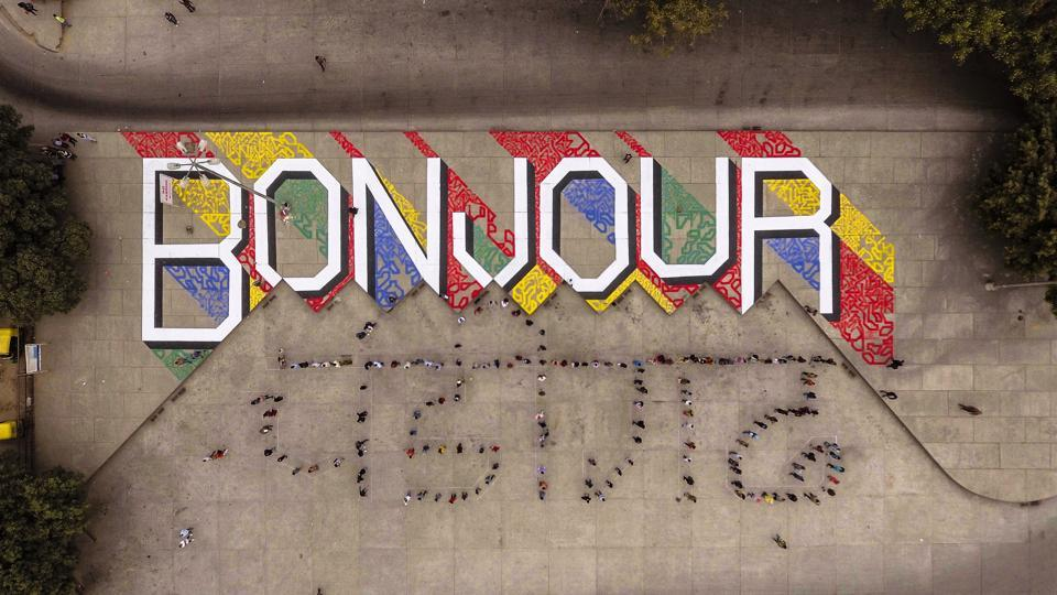 In a photo clicked using a drone, 'bonjour' (or 'good day' in French) as artwork and 'Chandigarh' written in Hindi by a human chain as part of a project of street art at the Sector-17 bus terminus in Chandigarh on Friday.