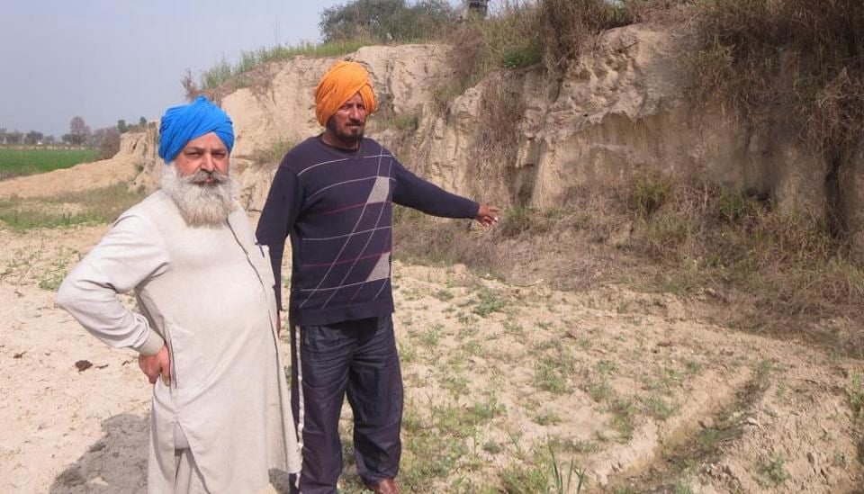 Local farmers showing the scarred landscape after the illegal mining near Janer village in Moga district.