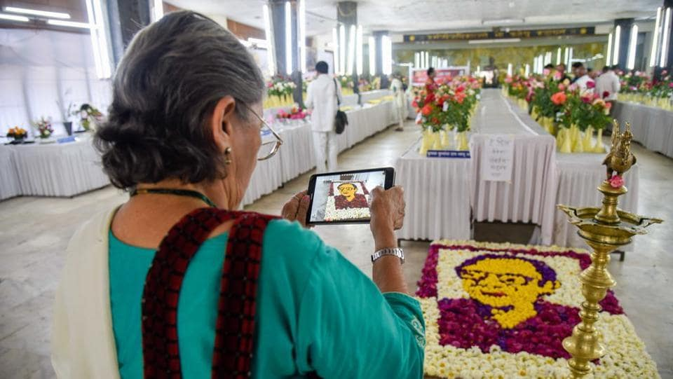 An elderly woman takes a picture of the roses exhibited at the rose show at Tilak Smarak Mandir on Tilak road on February 17. (Sanket Wankhade/HT PHOTO)