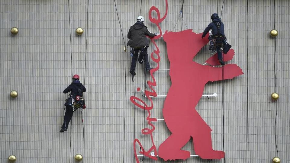 Employees install the Berlin Film Festival logo at a cinema in Berlin.