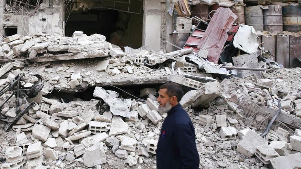 A man is seen near a damaged building in the besieged town of Douma, Eastern Ghouta.