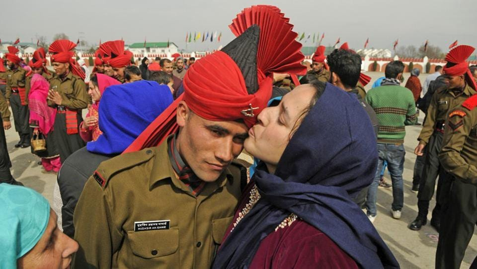 A relative kisses a new recruit after the graduation ceremony of the Jammu Kashmir Light Infantry Regiment (JKLIR) at an army base on the outskirts of Srinagar. (Waseem Andrabi  / HT Photo)