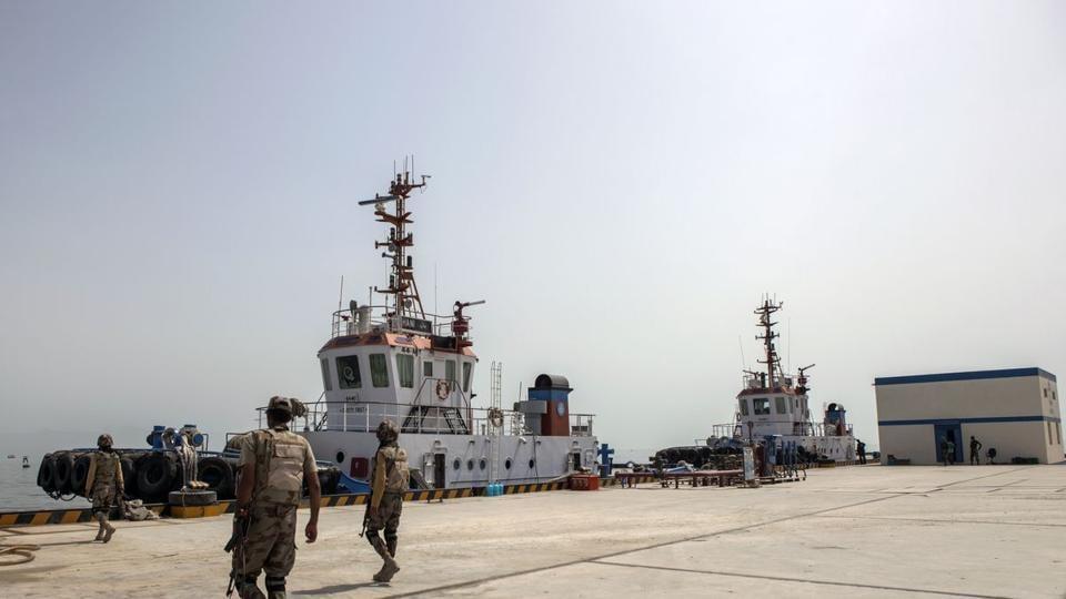 Members of the security forces walk along the dock at Gwadar Port in Gwadar, Balochistan, Pakistan.