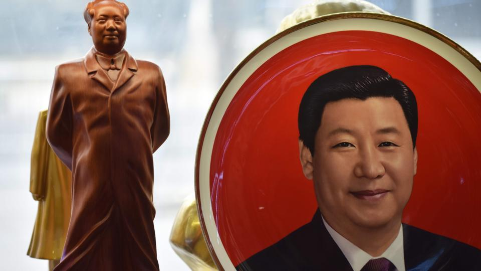 A decorative plate featuring an image of Chinese President Xi Jinping is seen beside a statue of late Communist leader Mao Zedong at a souvenir store next to Tiananmen Square in Beijing on February 27, 2018. China's propaganda machine has kicked into overdrive  to defend the Communist Party's move to scrap term limits for President Xi Jinping as critics on social media again defied censorship attempts.