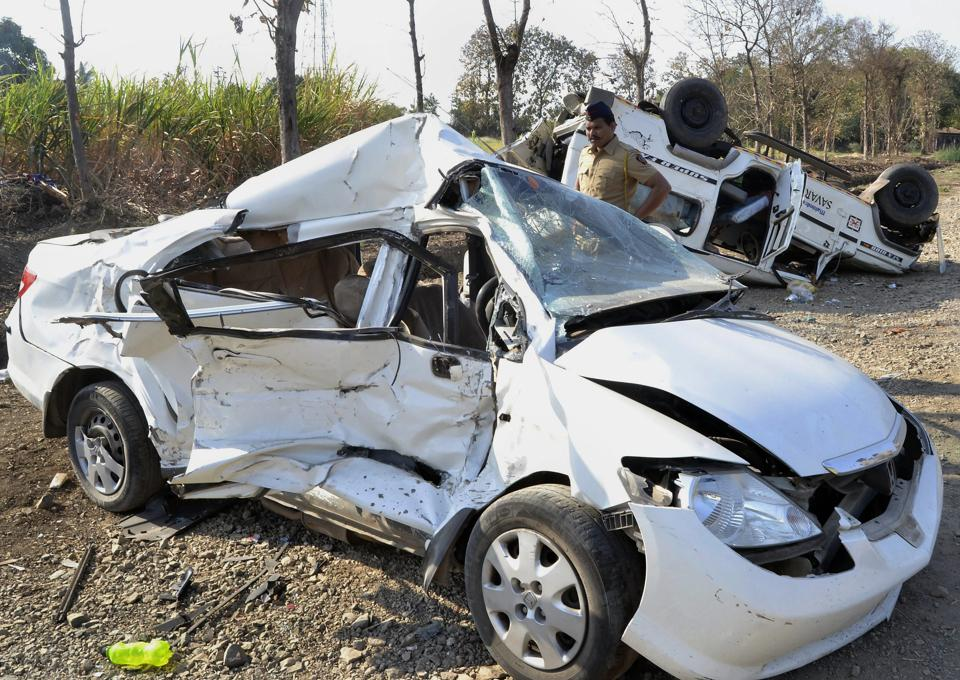 A policeman inspects a car that crashed into an SUV on Solapur-Tuljapur Road in Solapur on Tuesday. At least five people were killed and seven others injured during the mishap. (PTI)