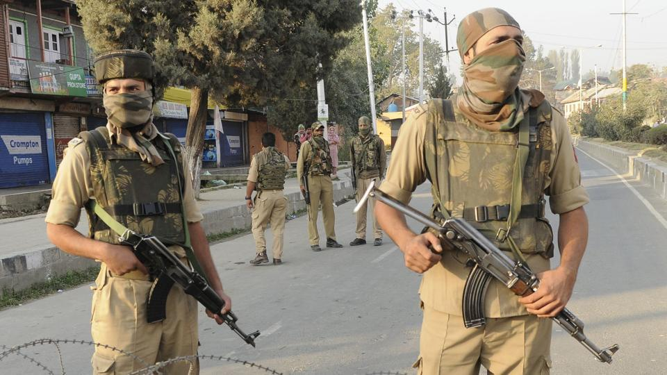 Policemen stand guard near the site of a gunfight between militants and forces near Srinagar airport in October 2017.