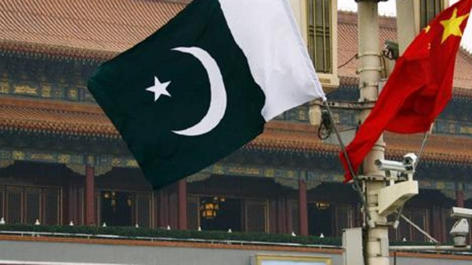 A Pakistan national flag flies alongside a Chinese national flag in front of the portrait of Chairman Mao Zedong on Beijing's Tiananmen Square.