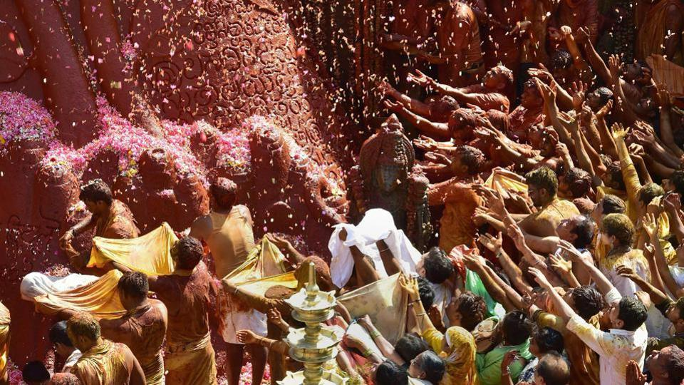 Devotees offer flower petals on the 58 feet monolithic statue of Gomateshwara or Lord Bahubali on the second day.  (PTI)