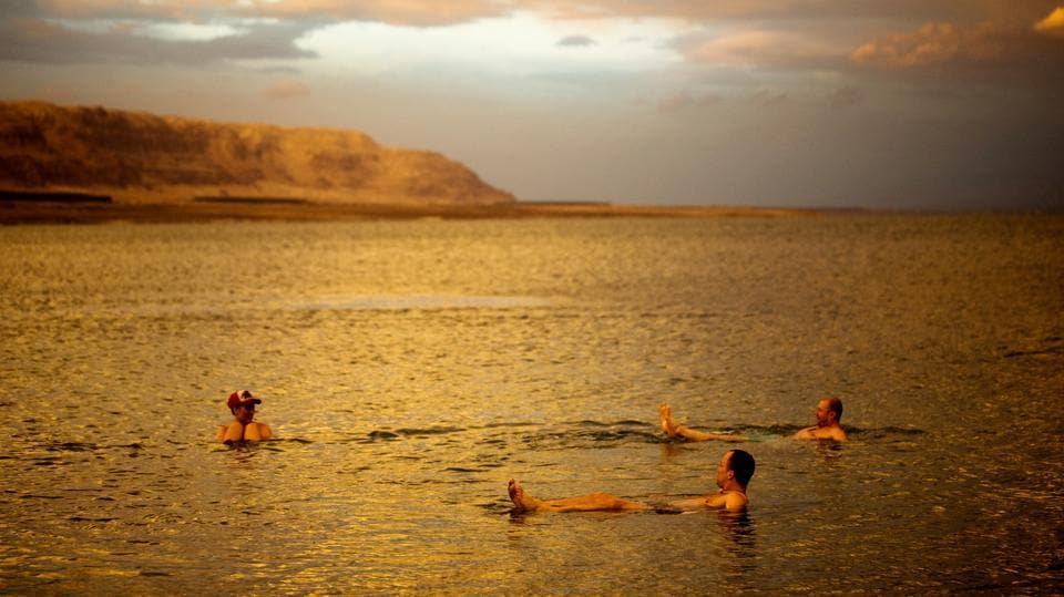 Tourists from Poland float in the Dead Sea during sunset near Metzoke Dragot. During high season in  winter when the heat is bearable, tourists flock here for getaways. Sufferers from chronic skin diseases, such as psoriasis and eczema, routinely make pilgrimages drawn by claims of the Sea's miraculous healing properties. (Ronen Zvulun / REUTERS)