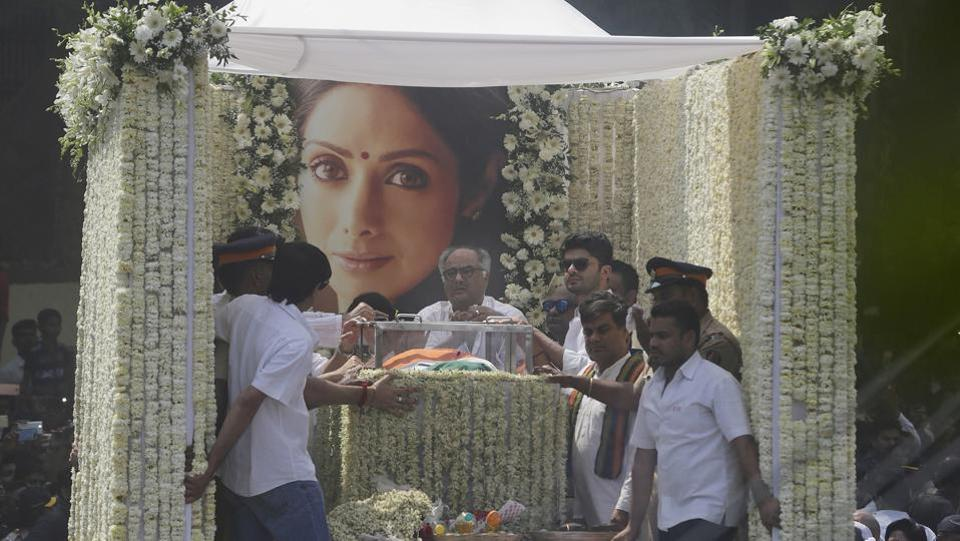 The late actor's husband Boney Kapoor (C), nephew Mohit Marwah and Arjun Kapoor were seen on the hearse as the procession made its way to the cremation ground with her body draped in the tricolour, followed by a large procession of mourners. (Rafiq Maqbool / AP)