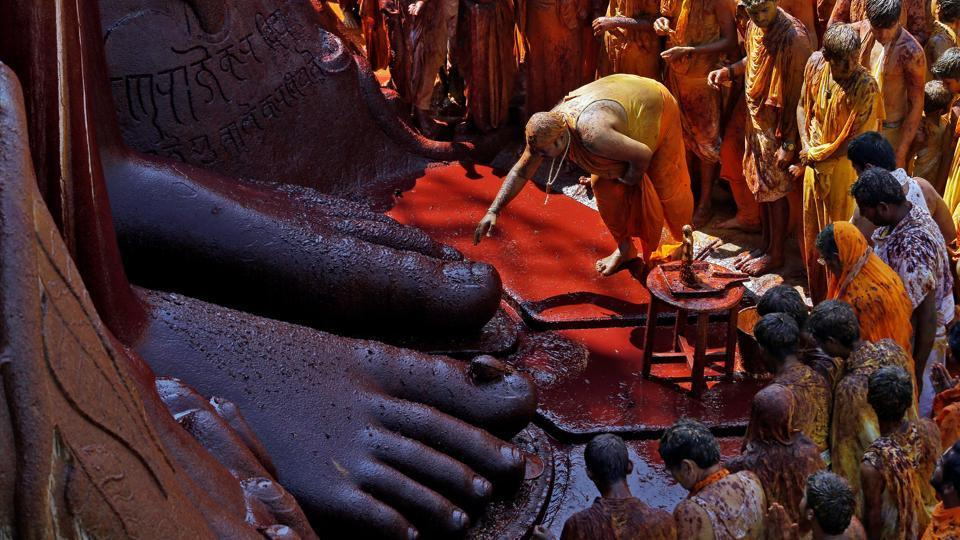 A devotee touches the feet of the monolithic statue of Jain deity Gomateshwara Bahubali as he celebrates the Mahamastakabhisheka, or the head-anointing ceremony of the statue, in Shravanabelagola. The ceremony unfolded on Saturday at this pilgrimage centre amidst a montage of traditional rituals.