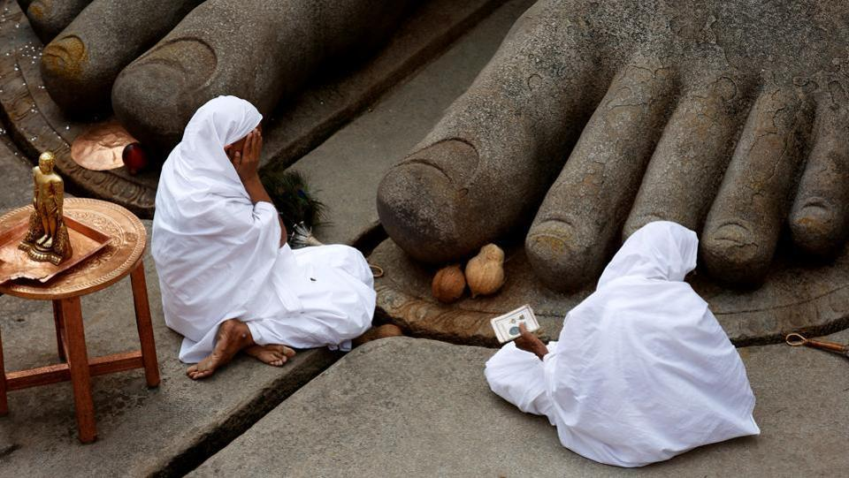 Women devotees sit at the feet of the monolithic statue of Jain deity Gomateshwara as they celebrate the anointing ceremony of the statue. While lakhs of people are thronging to the shrine to participate in what is also called as 'Jain Maha Kumbh', only several selected devotees made their way up the 618 steps leading to the statue. (REUTERS)