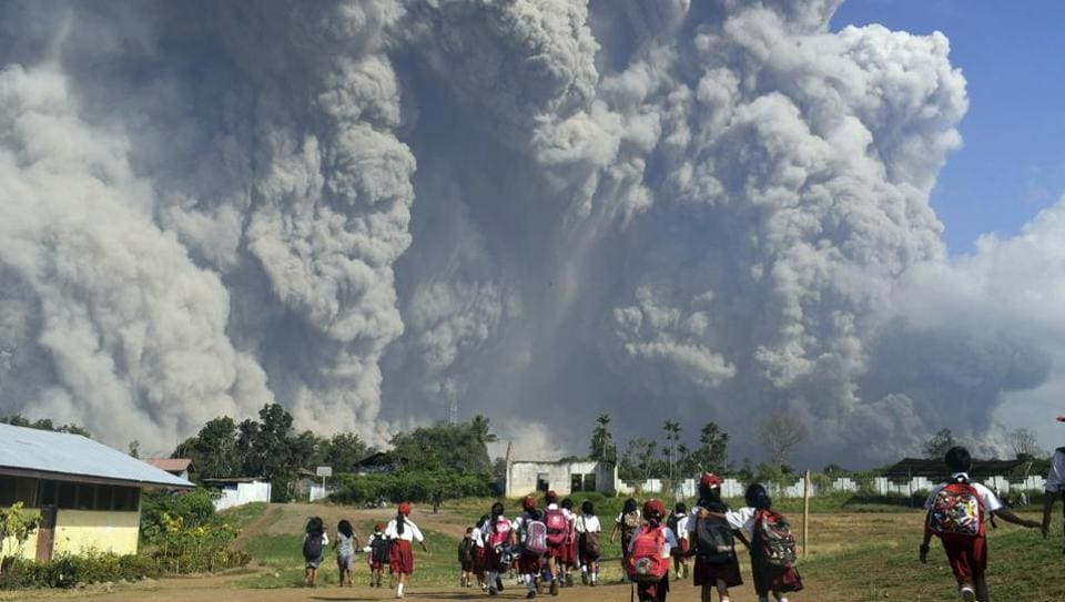 In this Feb. 19 2018, file photo, school children walk as Mount Sinabung erupts in Karo, North Sumatra, Indonesia. Rumbling Mount Sinabung on the Indonesian island of Sumatra has shot billowing columns of ash more than 5,000 meters (16,400 feet) into the atmosphere and hot clouds down its slopes