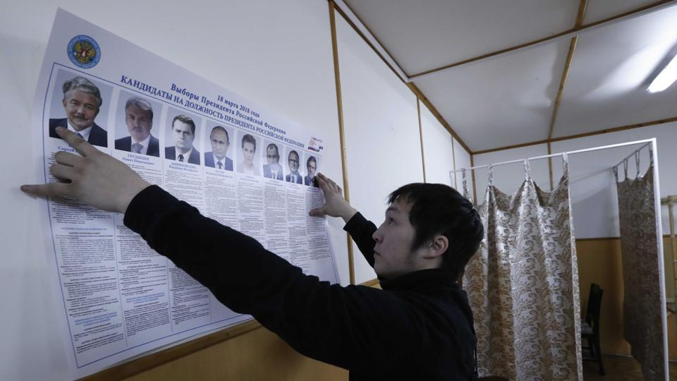 A member of a local electoral commission holds a broadsheet with information about the candidates during the early voting ahead of the March 18 presidential election in a settlement on the Pechora Sea island of Kolguyev in Nenets Autonomous District, Russia, on February 28, 2018.