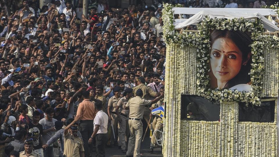 Indian fans watch as the funeral cortege of Sridevi passes through at Vile Parle in Mumbai.