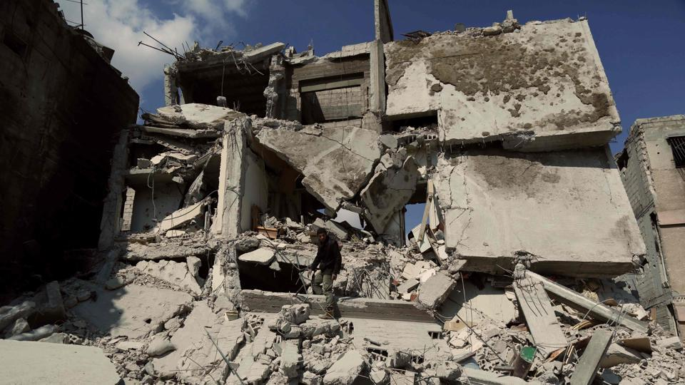 A Syrian man inspects the damage of a buildings which was destroyed earlier in regime air strikes, in the rebel-held besieged town of Douma in the eastern Ghouta region, on the outskirts of the capital Damascus, on February 28, 2018.