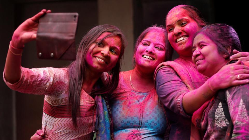 Teachers take a selfie during Holi celebrations, inside a school in Ahmedabad, on Thursday.