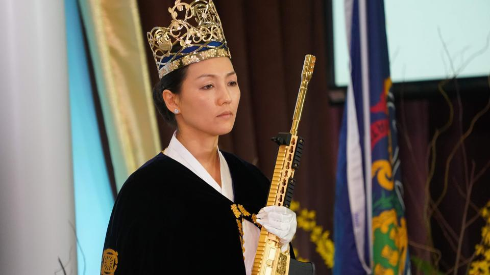 Yeon Ah Lee Moon, wife of controversial pastor Hyung Jin Moon, holds a weapon during service at World Peace and Unification Sanctuary in New Foundland, Pennsylvania. Dozens of couples donned crowns and cradled guns at a ceremony on Wednesday in a part of rural Pennsylvania that voted 68% for President Trump in 2016, underscoring the gulf between those who defend the US constitutional right to bear arms and advocates of gun control. (Don Emmert / AFP)