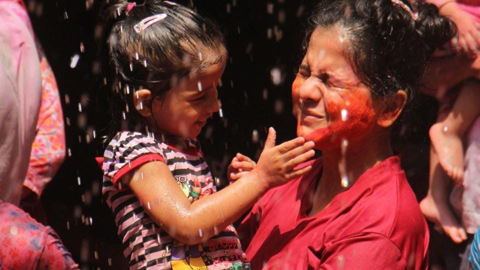 A small child plays with colour in the safety of her mother's arms.