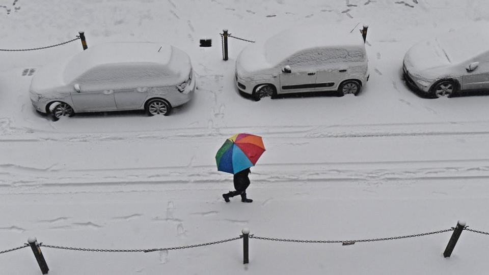 A woman shelters herself under a coloured umbrella as she walks in Florence, Italy. Meteorologists say that the cold spell could last for up to two weeks, and that even with temperatures expected to rise during the day next week, temperatures will most likely remain close to freezing at night. (Maurizio degl'Innocenti / AP)