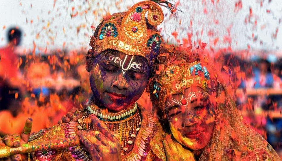 Tribal students from the Kalinga Institute of Social Science (KISS), dressed as Lord Krishna and Radha, are smeared with coloured powder and petals during Holi celebrations in Bhubaneswar. (Asit Kumar / AFP)