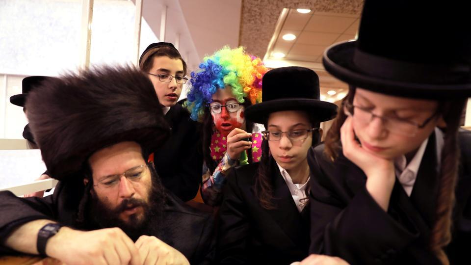 A boy dressed up in a Purim costume looks on as ultra Orthodox Jews take part in the reading from the Book of Esther, a ceremony performed on the Jewish holiday of Purim, in Jerusalem. (Ammar Awad / REUTERS)