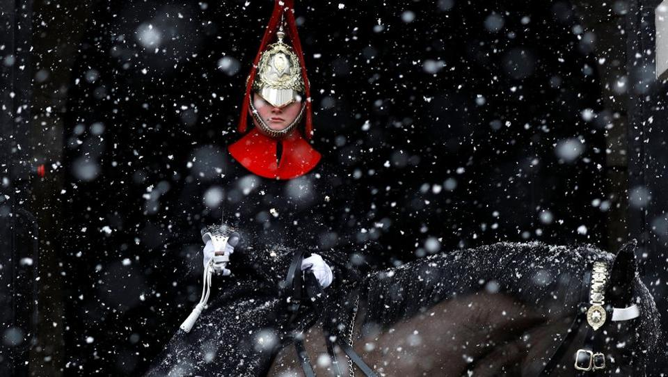 A guardsman sits on duty in the snow at Horse Guards Parade in London. (Peter Nicholls / REUTERS)