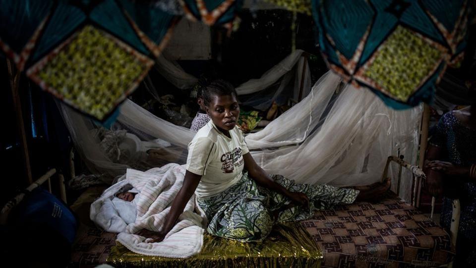 An Internally Displaced Congolese woman rests with her new born child in a clinic for IDP's just out side the camp in Bunia. Twenty-three people were killed in renewed clashes between ethnic groups in the Democratic Republic of Congo's troubled east. (John Wessels / AFP)