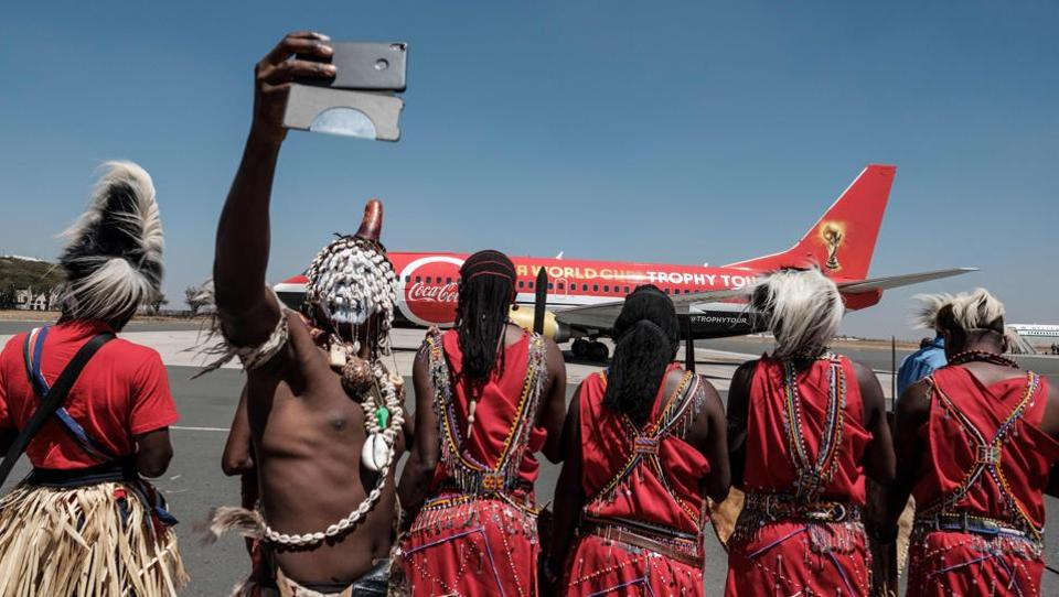 A dancer takes a picture upon the arrival of the special aircraft carrying the FIFA World Cup Trophy during its World Tour at the Jomo Kenyatta International airport in Nairobi. (Yasuyoshi Chiba / AFP)