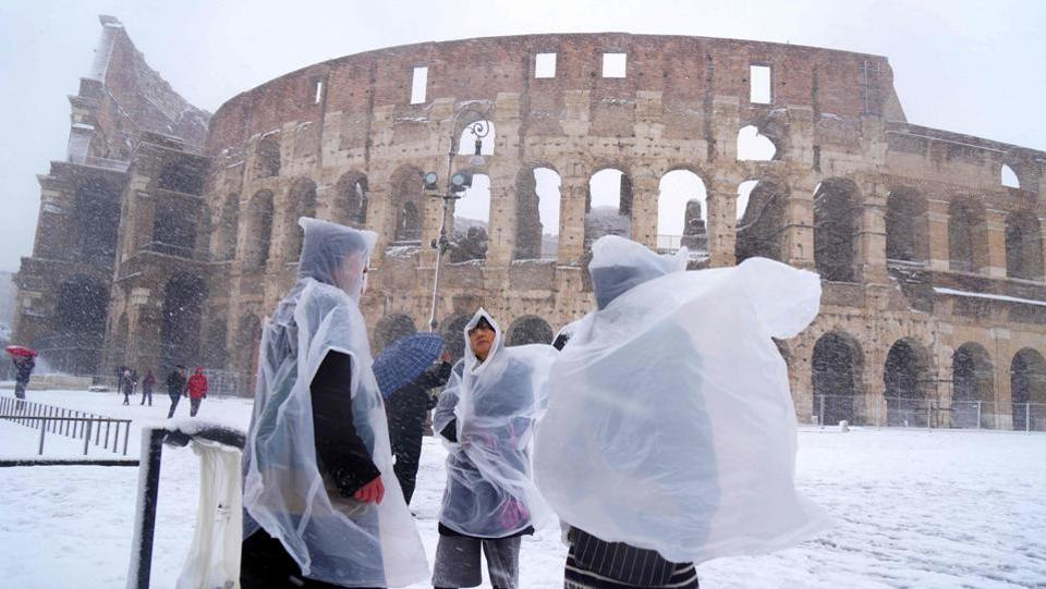 Japanese tourists put on plastic coats as they visit the ancient Colosseum during a the first snowfall in six years in Rome. (Vincenzo Pinto / AFP)