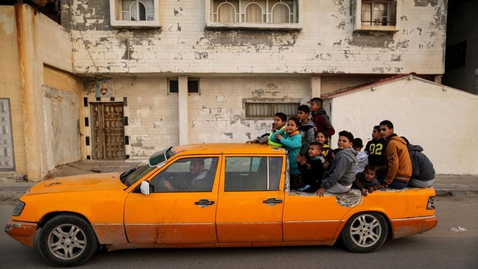 Palestinian children sit on the back of a Mercedes 6-door taxi converted into a pick-up vehicle in the al-Shatee refugee camp in Gaza City. (Mahmud Hams / AFP)