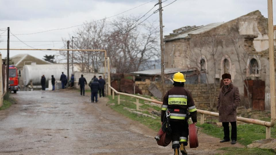 A firefighter carrying fire hoses walks near the scene of a fire which broke out in a drug abuse treatment center in Baku, Azerbaijan March 2, 2018.