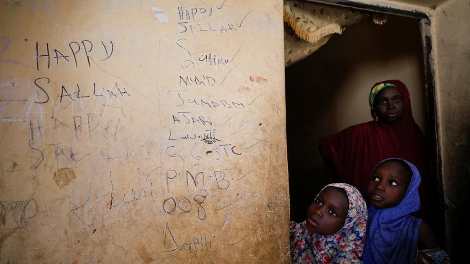 Fatima Dala's mother and sisters stand by a wall covered in her writings at their home, in Jumbam village, Nigeria. Fatima was among the 110 students abducted by Boko Haram militants from the Government Girls Science and Technical College in Dapchi, a dusty, remote town in the northeast Nigerian state of Yobe on February 19. (Afolabi Sotunde / REUTERS)