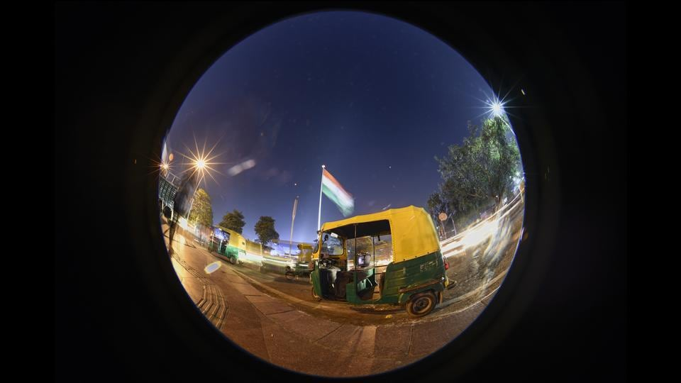 Seen behind the autorickshaw, the 207-foot-tall flag at Central Park in CP was installed by the Flag Foundation of India, a Delhi-based nonprofit set up by Indian steel magnate Naveen Jindal to encourage Indians to feel proud to fly the national flag.  (Burhaan Kinu / HT Photo)