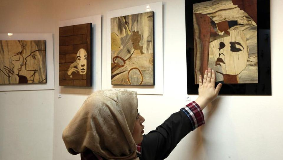Iranian victims of acid attacks present their work at the Ashianeh gallery in Tehran to raise awareness and money.