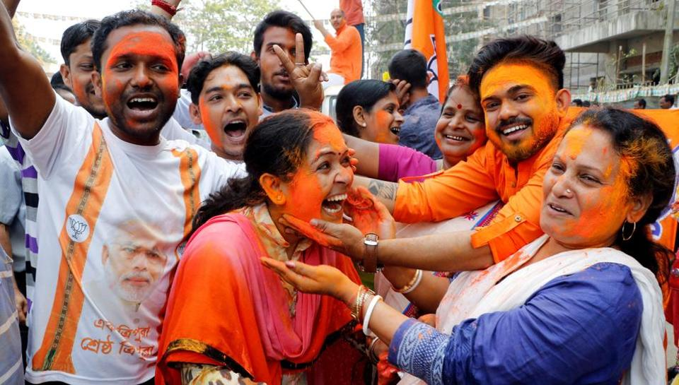 A supporter of India's ruling Bharatiya Janata Party (BJP) reacts as others apply colour powder on her face while they celebrate after learning of the initial poll results of Tripura state assembly elections, in Agartala on March 3, 2018.