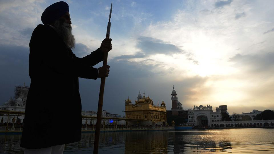 An Sikh Sewadar volunteer stands near the Sikh Golden Temple as dark clouds are seen over it, in Amritsar. (Narnder Nanu / AFP)