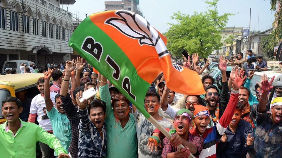 BJP supporters wave party flag to celebrate BJP's lead in Tripura assembly elections, in Agartala.
