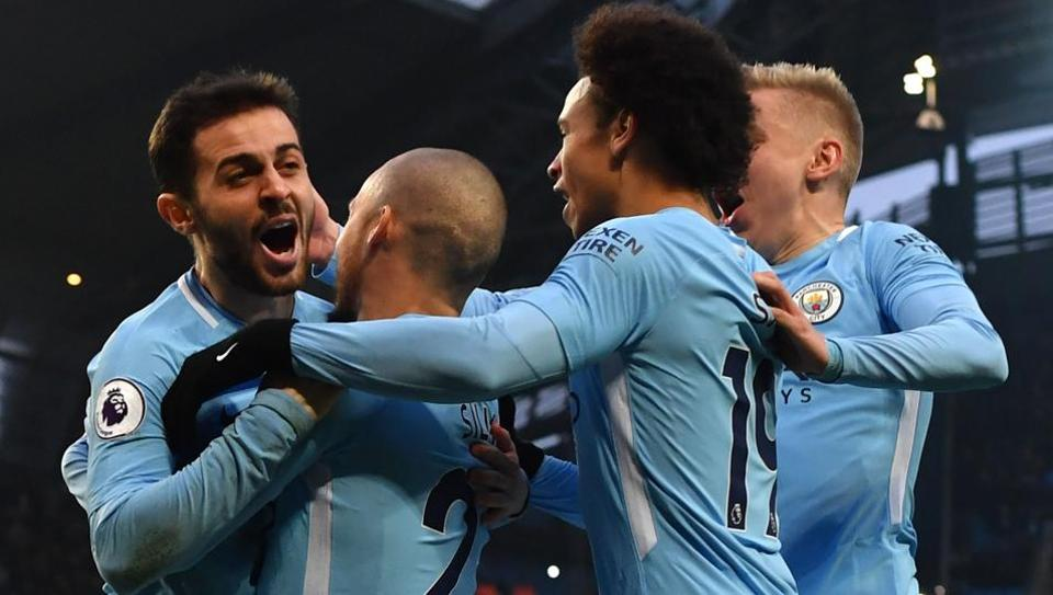 Manchester City's Bernardo Silva (L) celebrates scoring the opening goal with teammates during the English Premier League football match between Manchester City and Chelsea at the Etihad Stadium in Manchester, north west England on March 4, 2018.