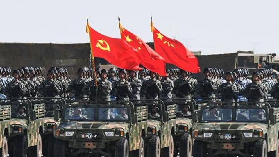 This file picture taken on July 30, 2017 shows Chinese soldiers carrying the flags of (L to R) the Communist Party, the state, and the People's Liberation Army during a military parade at the Zhurihe training base in China.