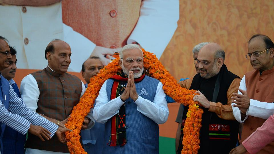 Prime Minister Narendra Modi gestures as he is garlanded by BJP leaders during the election results of three northeast states at the BJP headquarters in New Delhi on March 3.