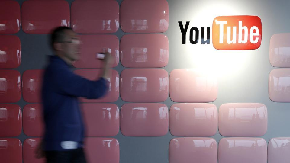 A video creator walks past Google Inc.'s YouTube logo displayed at the company's YouTube Space studio in Tokyo, Japan.