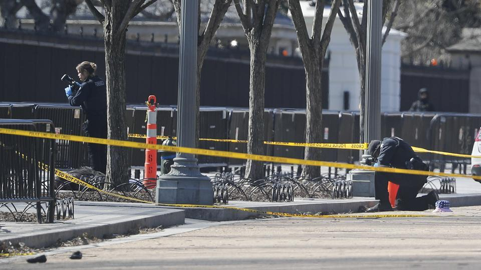 Law enforcement officers photograph the shooting site in front of the White House in Washington, which is close to pedestrian traffic, Saturday, March 3, 2018. A