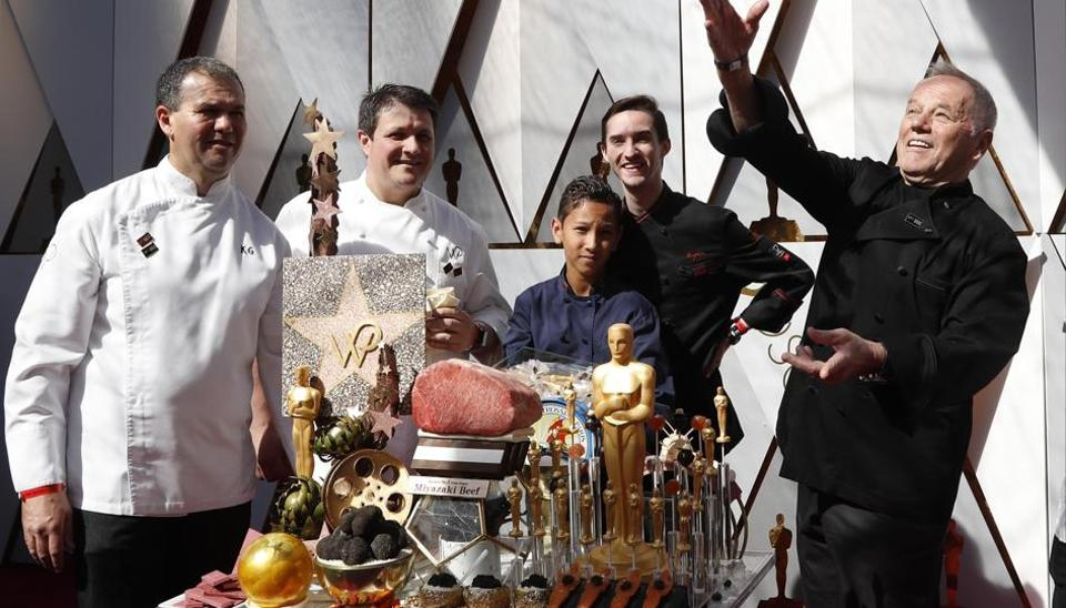 Celebrity chef Wolfgang Puck (extreme right) throws candy statuettes on the red carpet.