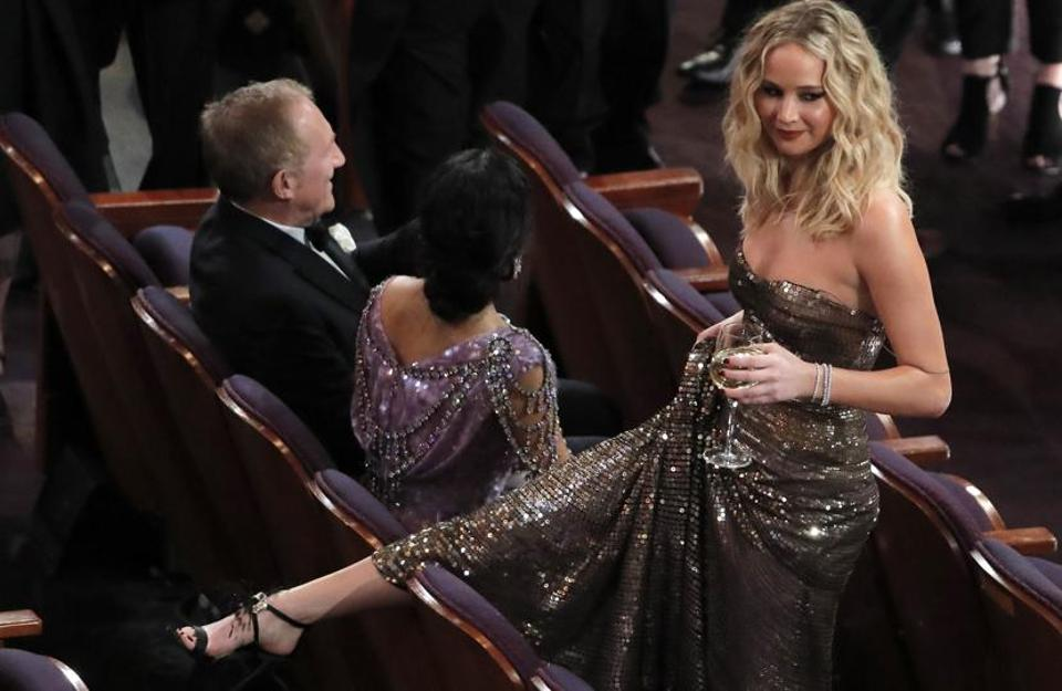 Salma Hayek and her husband Francois-Henri Pinault sit as Jennifer Lawrence attempts to skip over seats.