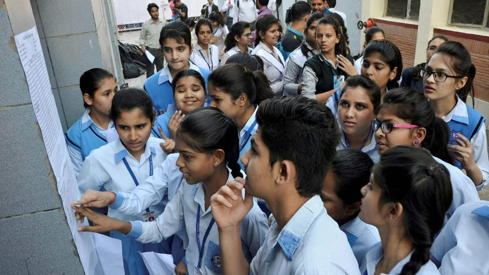 Students check their roll numbers on a notice board for seat allocation outside an examination centre for CBSE board exams in Gurugram on Monday.