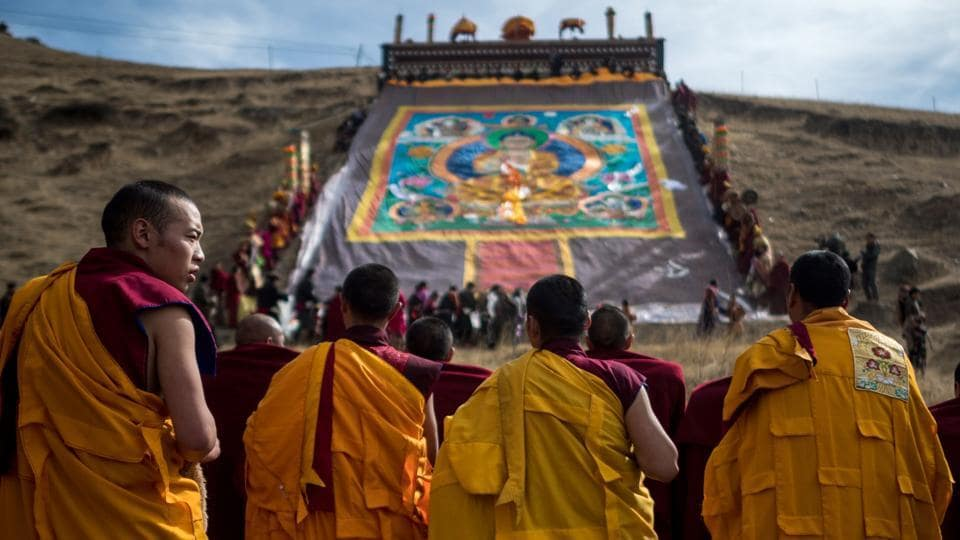 Tibetan Buddhist monks unveil a giant thangka painting for Monlam, otherwise known as the Great Prayer Festival of Losar.