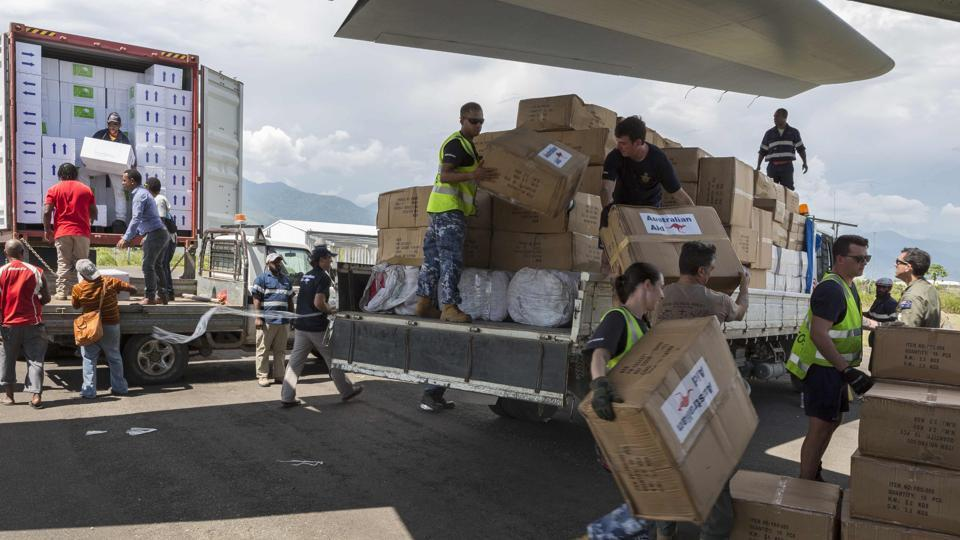 Air force personnel along with Australian High Commission officials and Papua New Guinean locals unloading humanitarian aid from trucks onto an RAAF C-130J aircraft in Lae, bound for earthquake-affected areas in the Papua New Guinea highlands.