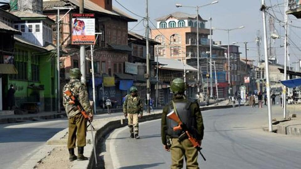 Security personnel patrol a street during restrictions in Srinagar.